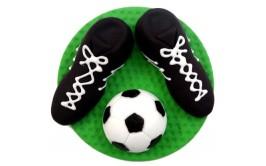 בסיס ירוק ועליו נעלי כדורגל וכדור מבצק סוכר